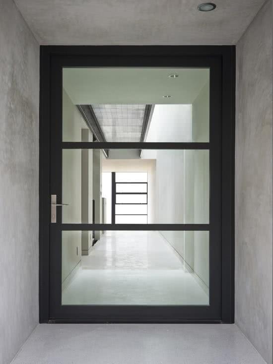 Porta ebanizada envolta de vidros e puxador em inox