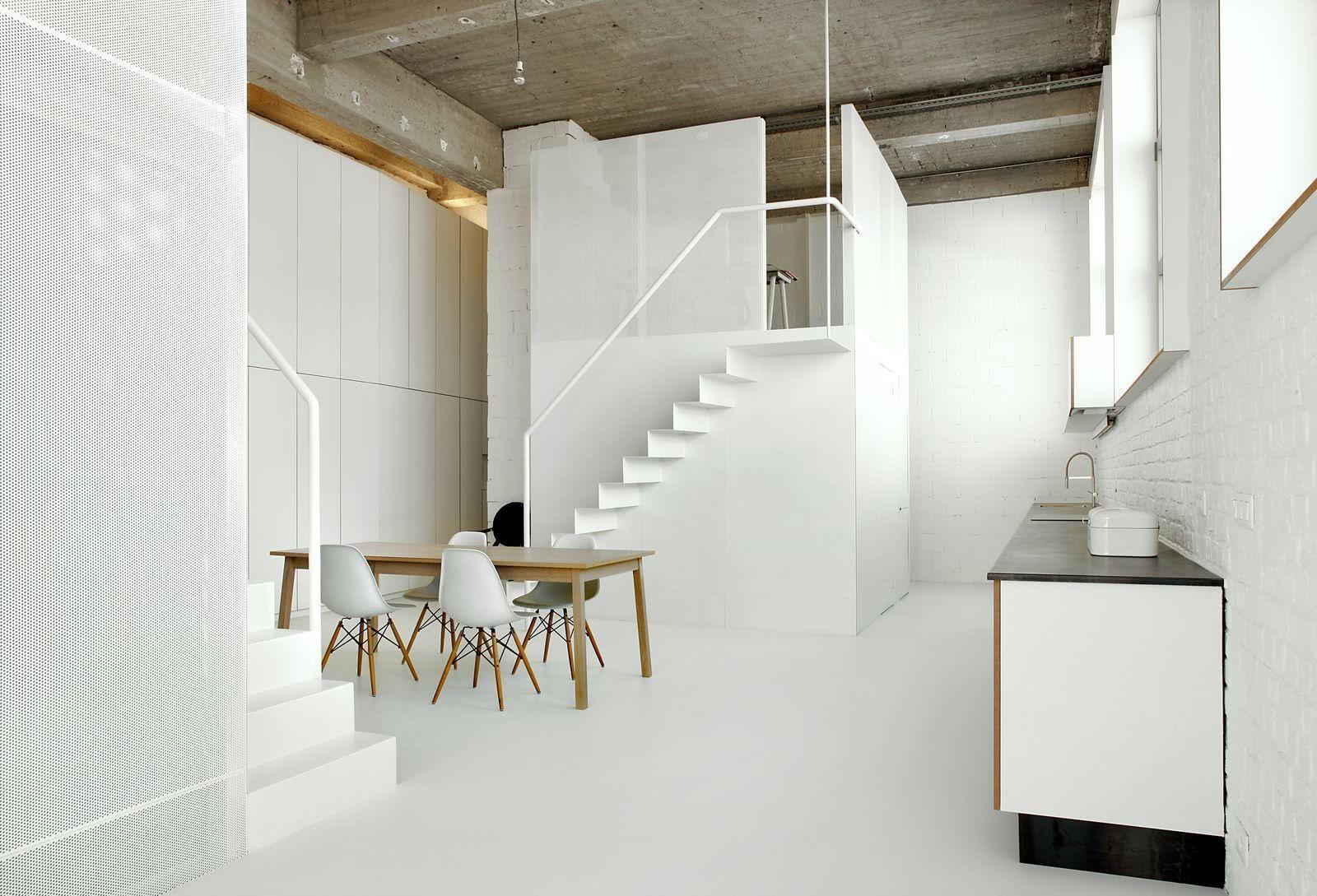 Loft com móveis em branco e teto em concreto