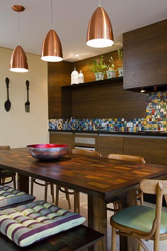 Varanda gourmet com detalhes em cobre nas luminárias