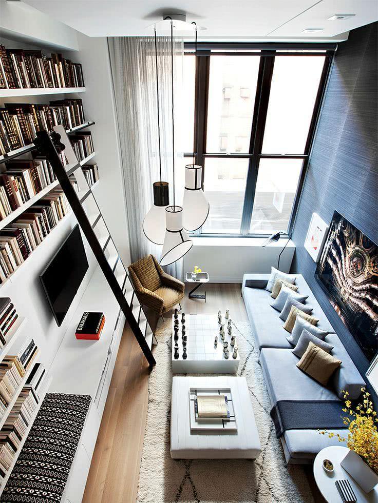 Sala de loft com prateleiras de livros acima da TV