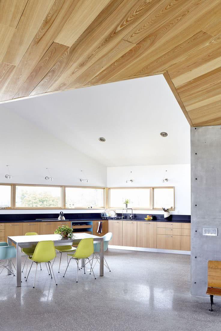 Cozinha com amplas janelas e cadeiras coloridas