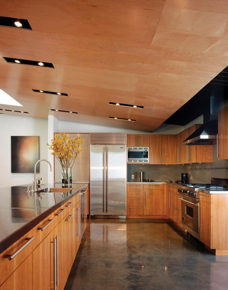 Cozinha moderna com bancada de inox egabinetes de madeira