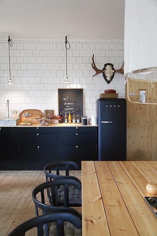 Cozinha com geladeira preta e gabinetes na mesma cor