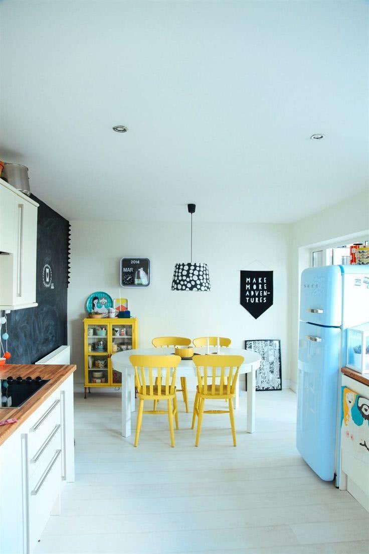 Cozinha com cadeiras amarelas e geladeira azul clara no estilo retrô