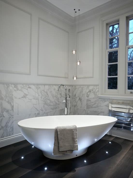 Banheira branca, parede revestida de pedra