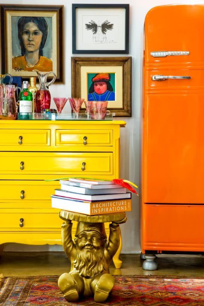 Nesta proposta, a geladeira com cor laranja vibrante combina com o móvel amarelo