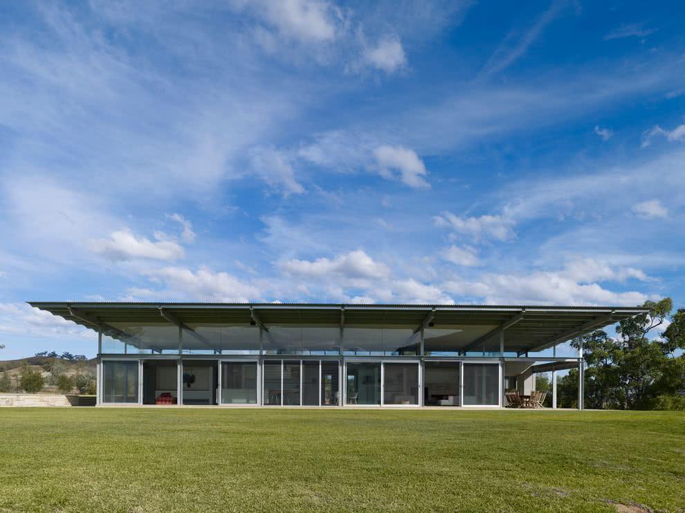 Ampla casa de campo moderna com um grande gramado.