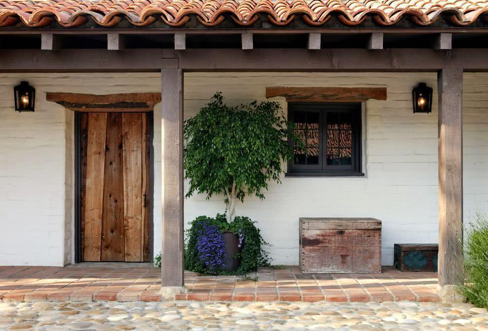 Casa de campo com tijolos pintados de branco e madeiras no estilo rústico.