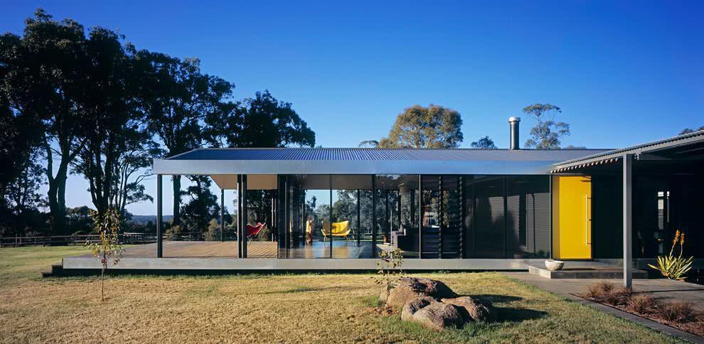 Um projeto moderno de casa de campo térrea com varanda e porta amarela.