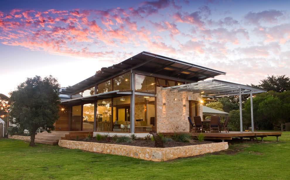 Casa com vidros que proporcionam uma ampla visão do campo. Além do telhado, há um pergolado metálico na área externa.