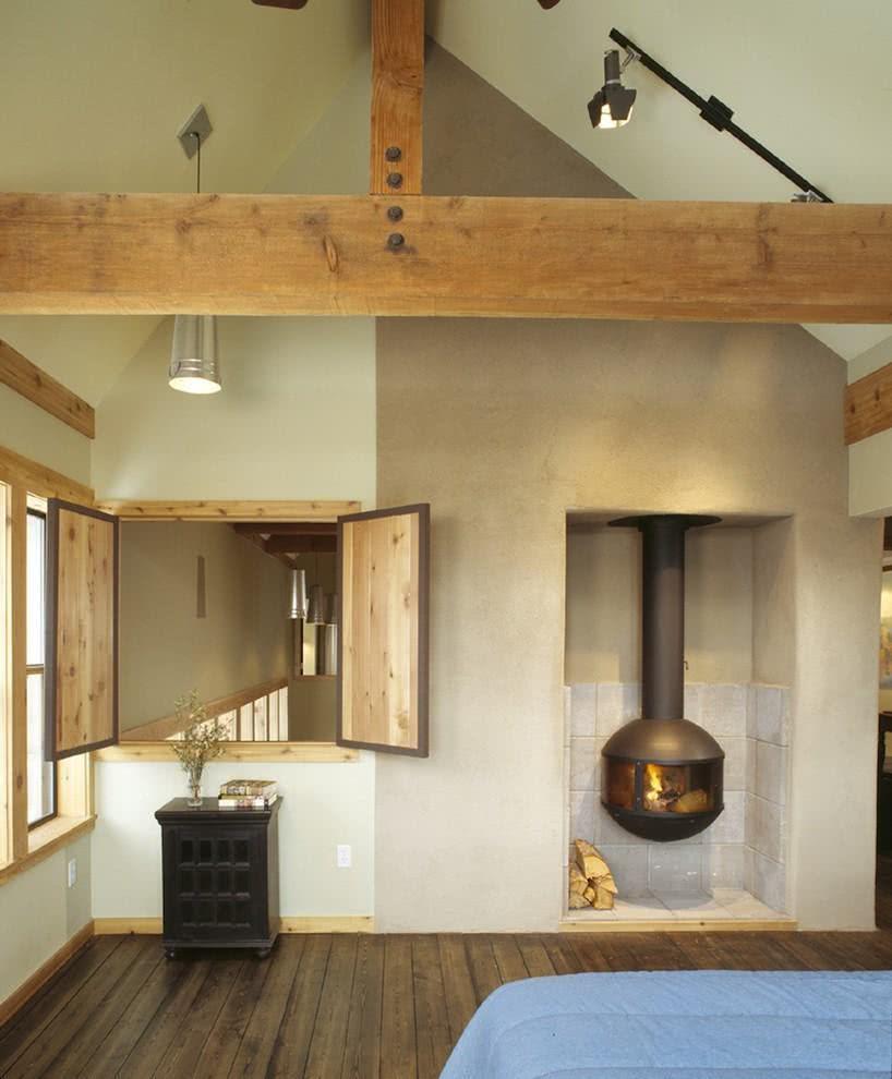 Quarto decorado com lareira e tons rústicos da madeira, sem perder a modernidade.
