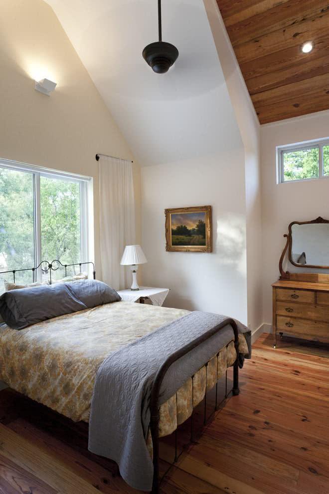 Quarto clean em casa de campo com detalhes de madeira.