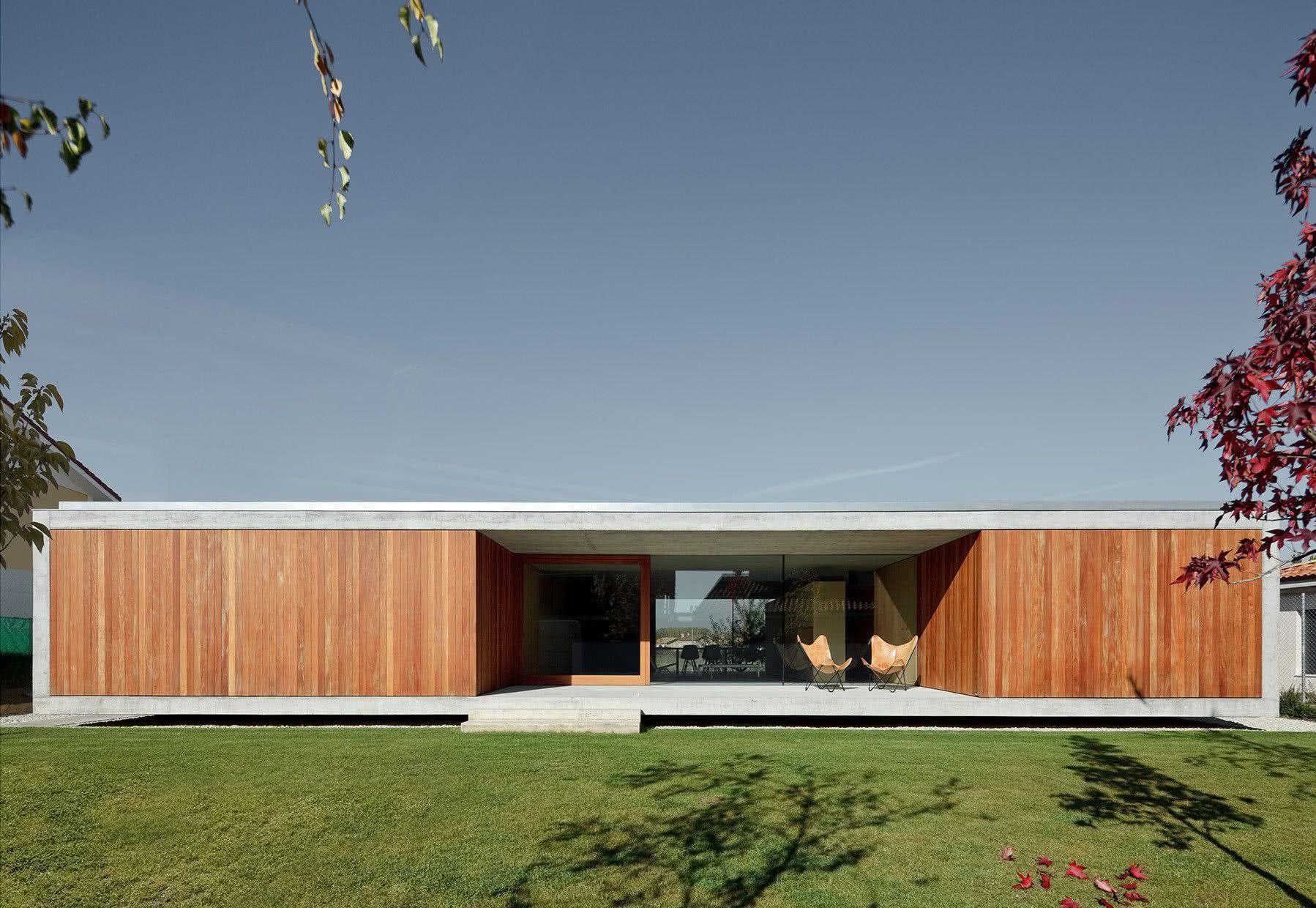 Casa térrea moderna de concreto e revestimento frontal de madeira.