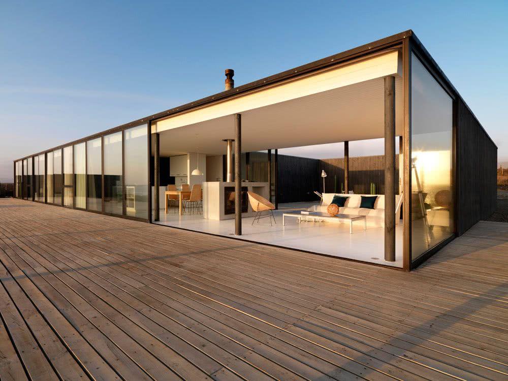 Casa térrea com estrutura metálica e deck de madeira.