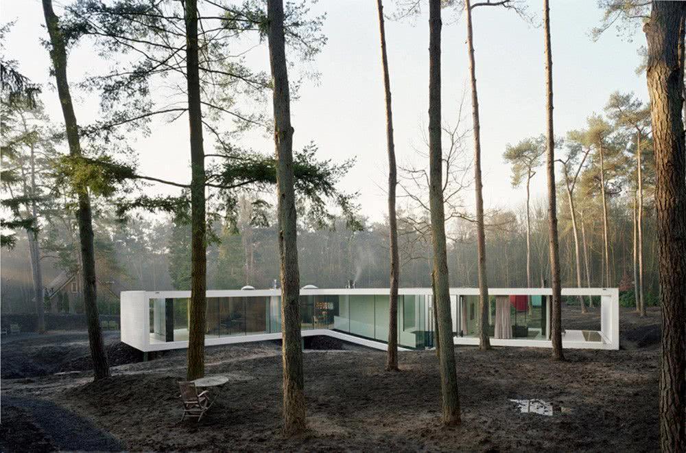 Casa térrea na floresta com painéis de vidro.