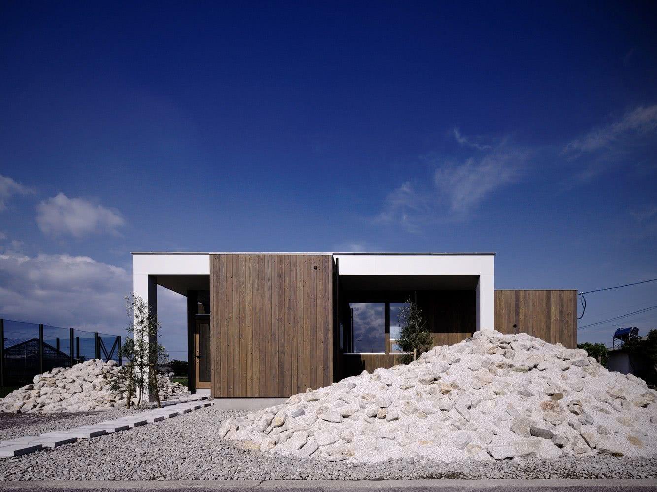 Casa térrea pequena com pintura branca e revestimento em madeira.
