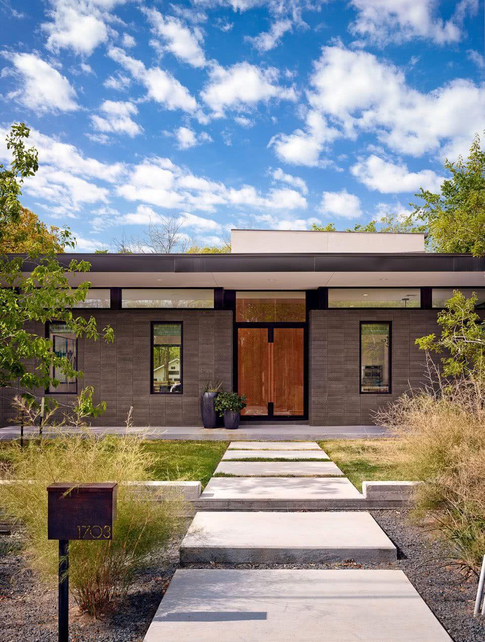 Fachada de casa térrea em bloco de concreto e porta de madeira.