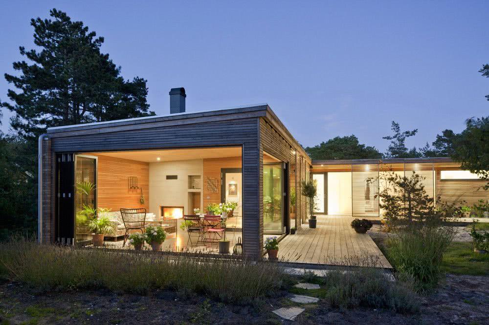 Fachada de casaem madeira com painéis de vidro.