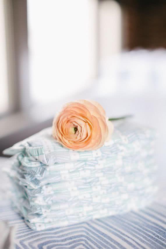 As fraldas como centro de mesa. Para dar um toque charmoso, a rosa é a cereja do bolo