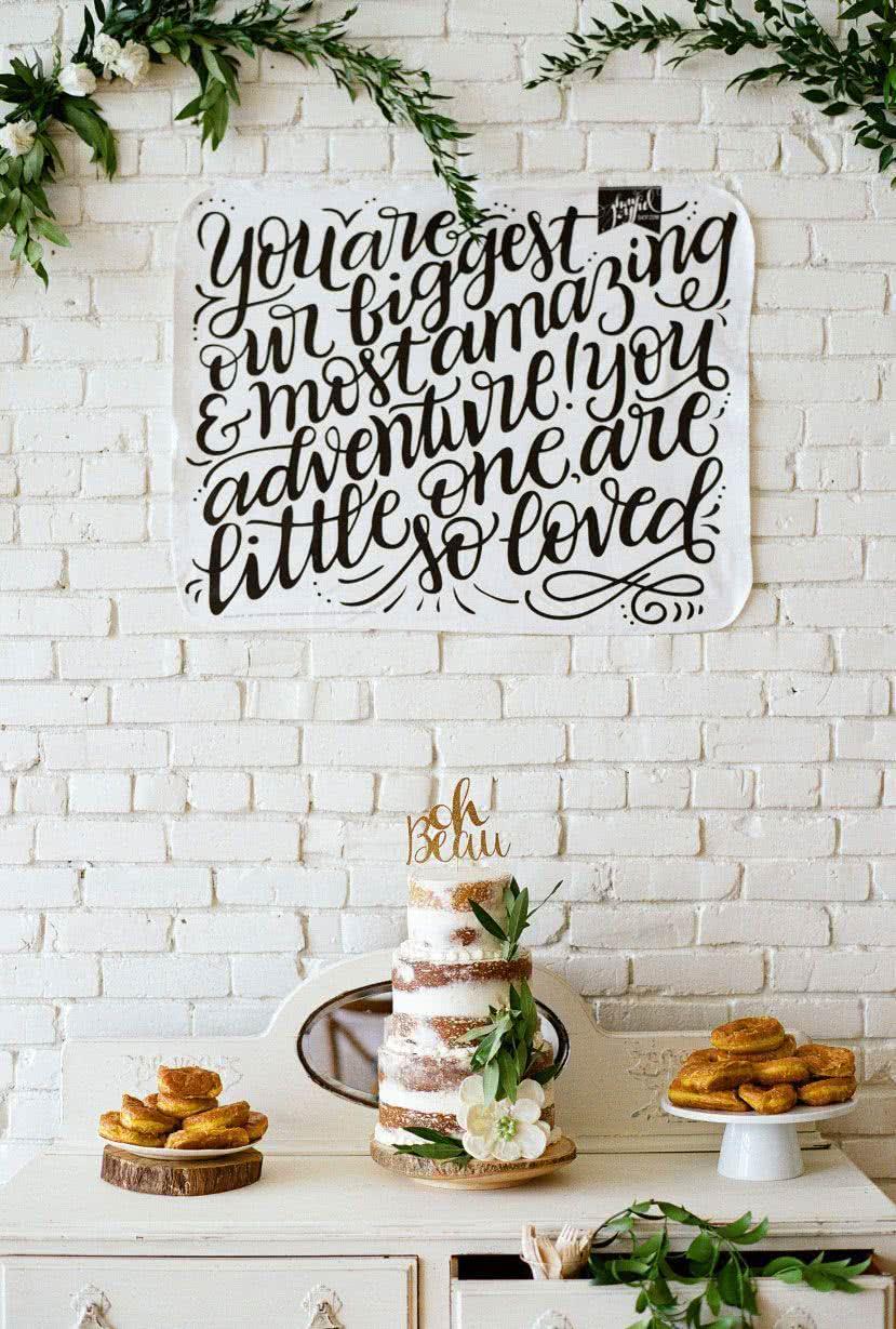 """Para os papais minimalistas e modernos. Na parede, uma mensagem emocionante escrita à mão livre: """"Você é a nossa maior e mais incrível aventura"""