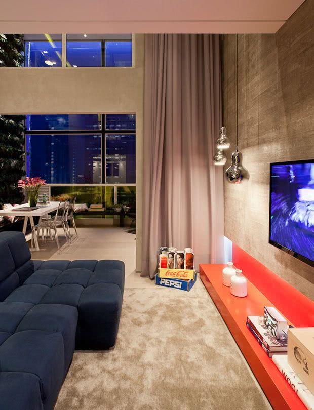 Sala simples e elegante com bancada baixa vermelha e TV fixa na parede de concreto