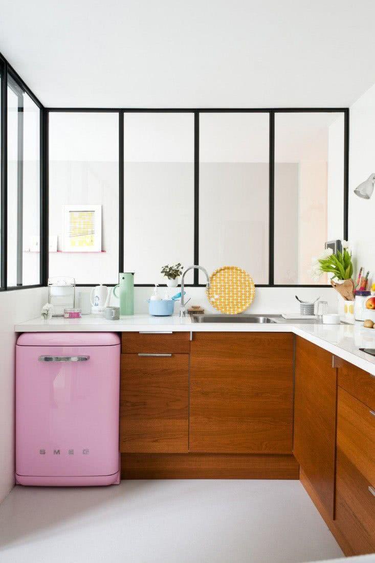 Frigobar rosa junto aos gabinetes da cozinha