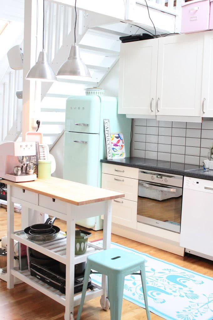 Cozinha clara com banqueta e geladeira verde água