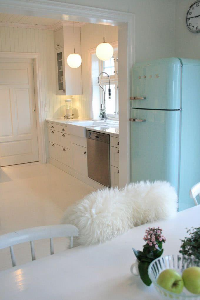 Cozinha branca com geladeira verde água