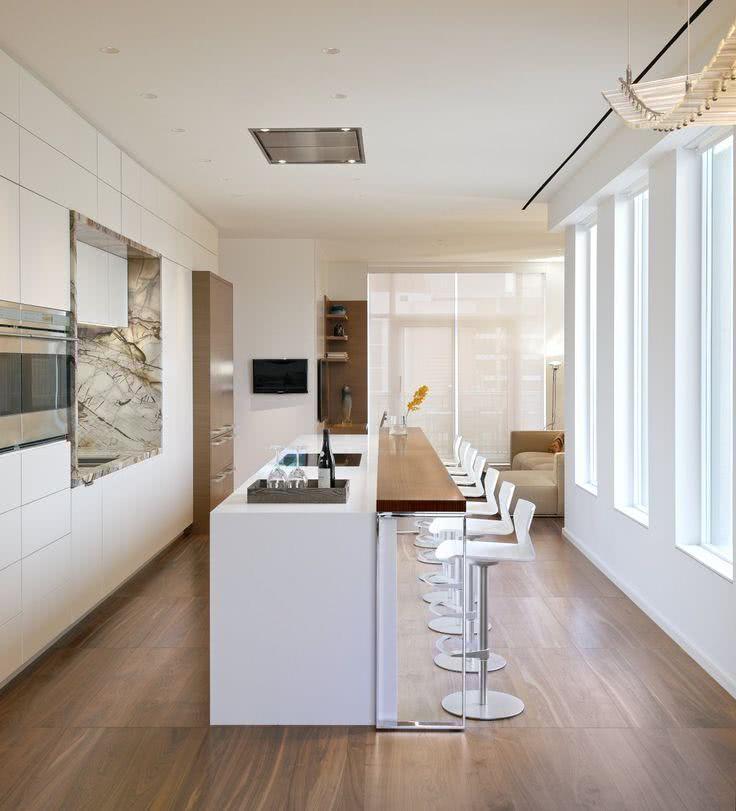 Cozinha branca com piso de madeira