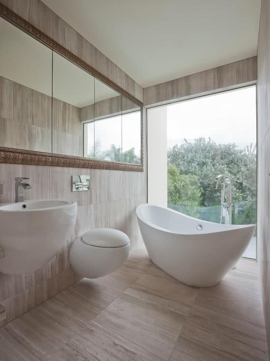 Banheiro com revestimento de madeira e banheira branca