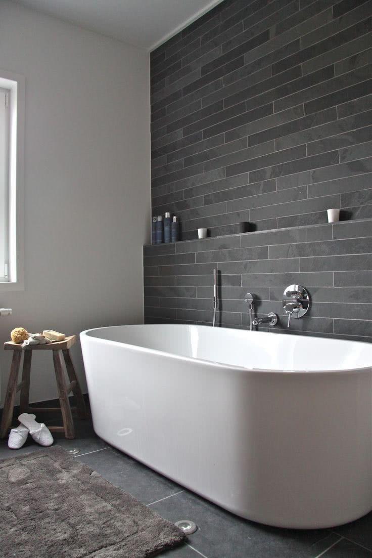 Parede de pedra escura e banheira branca simples