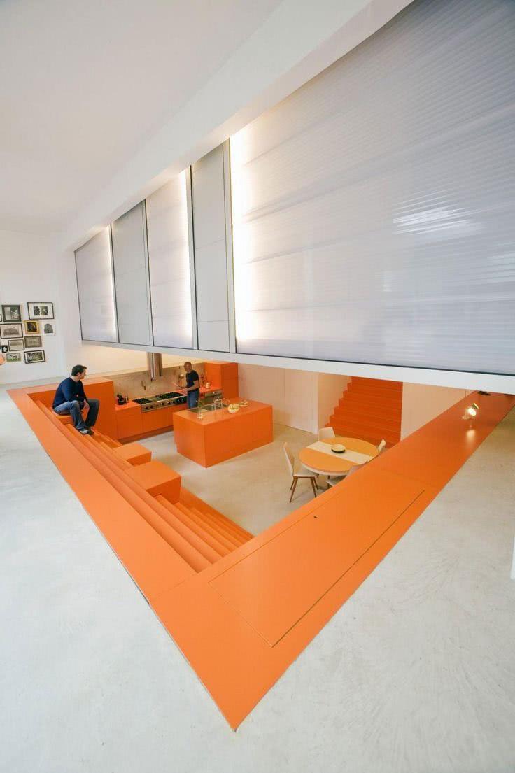 Cozinha tipo porão com escada e bancada unidas na cor laranja