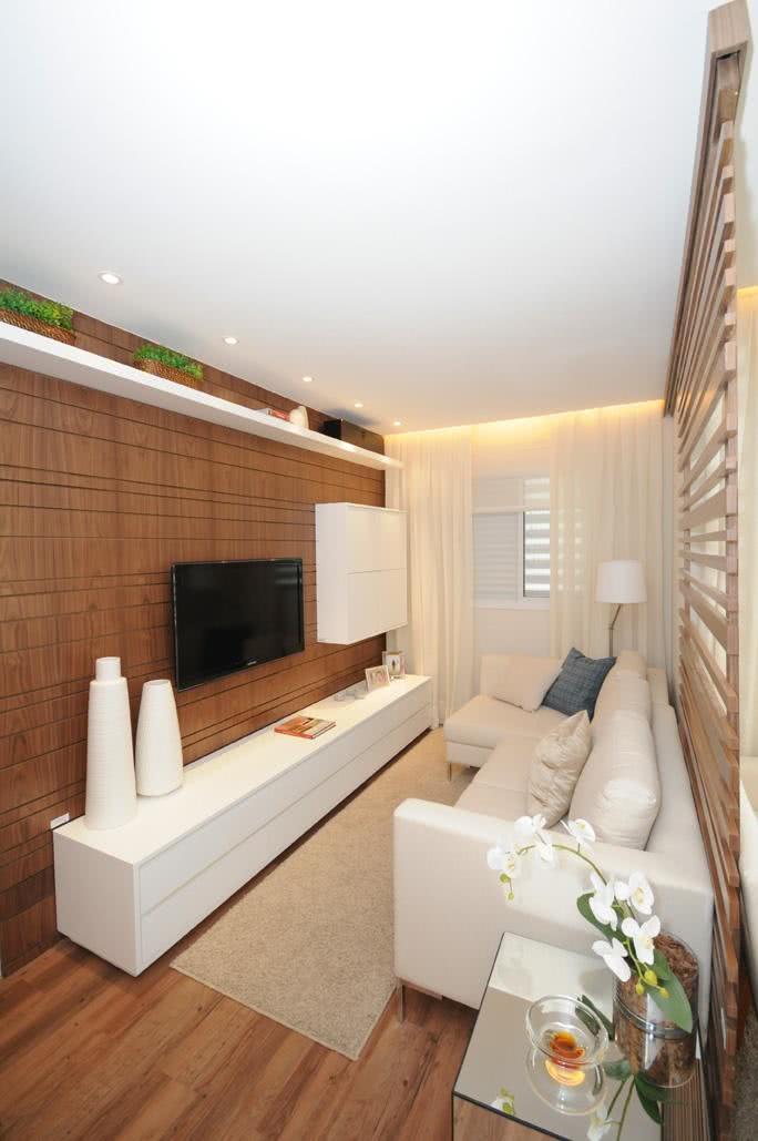 Sala com parede de madeira e TV fixa na parede