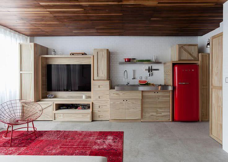 Cozinha com caixotes de madeira e detalhes na cor vermelha