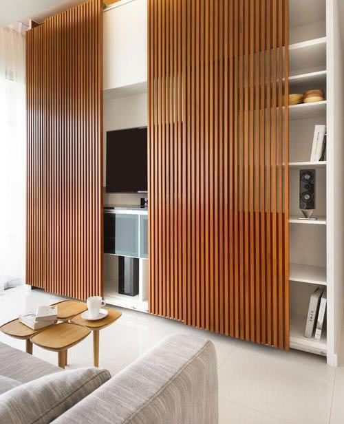 Armário com portas de madeira vazada na sala de TV decorada