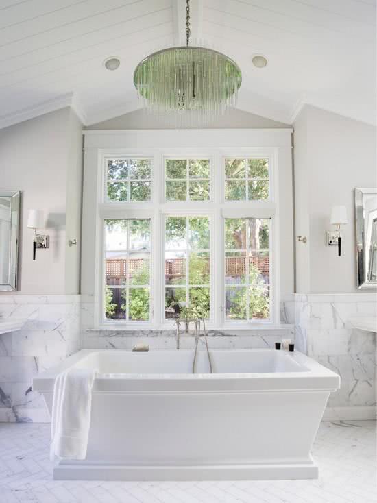 Banheiro com pedras e banheira grande retangular