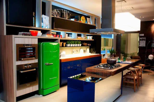 Cozinha que combina o gabinete azul marinho com a geladeira verde