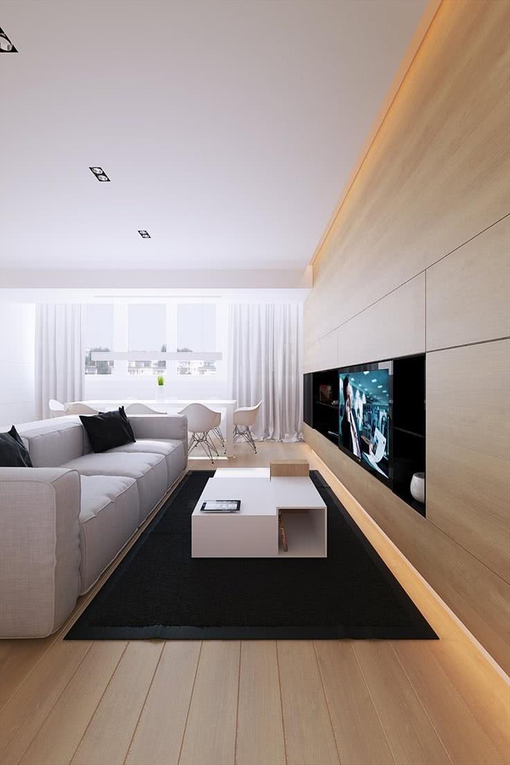 Sala com parede de madeira clara e TV acoplada
