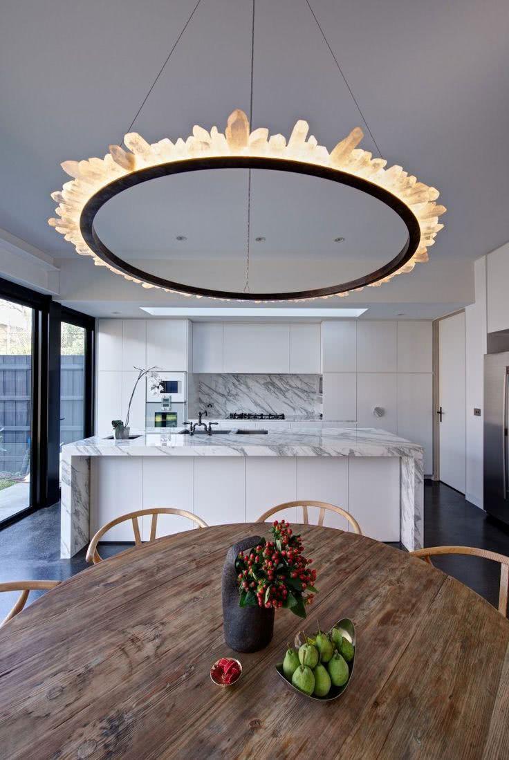 Cozinha branca com bancada de pedra e lustre circular