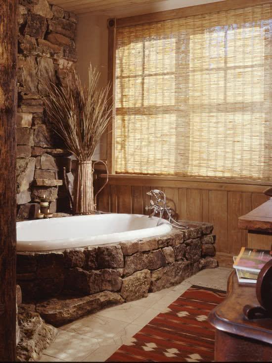 Banheira branca com revestimento de pedras ao redor