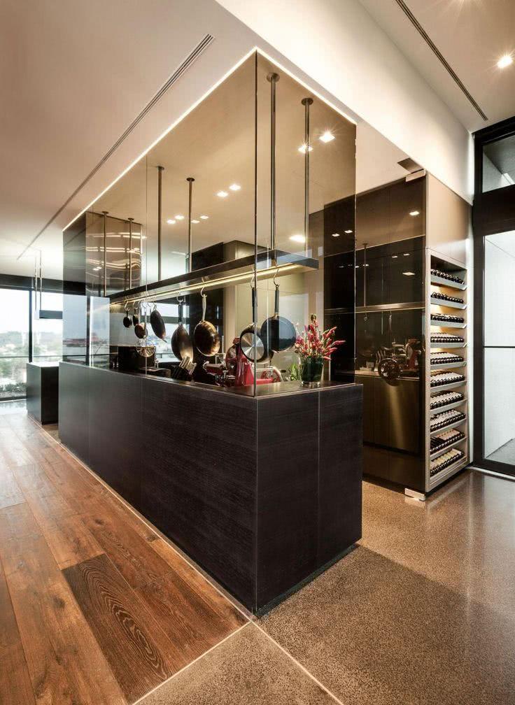 Cozinha com piso de madeira e ilha preta retangular com vidros