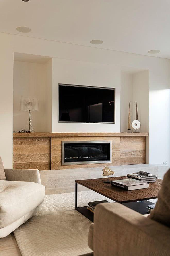 Sala com TV acoplada acima da lareira