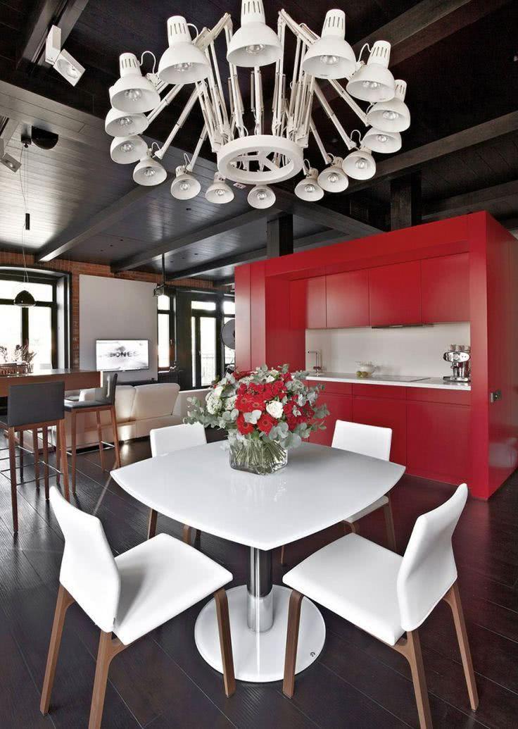 Cozinha com móvel vermelho, destaque para o lustre feito de spots