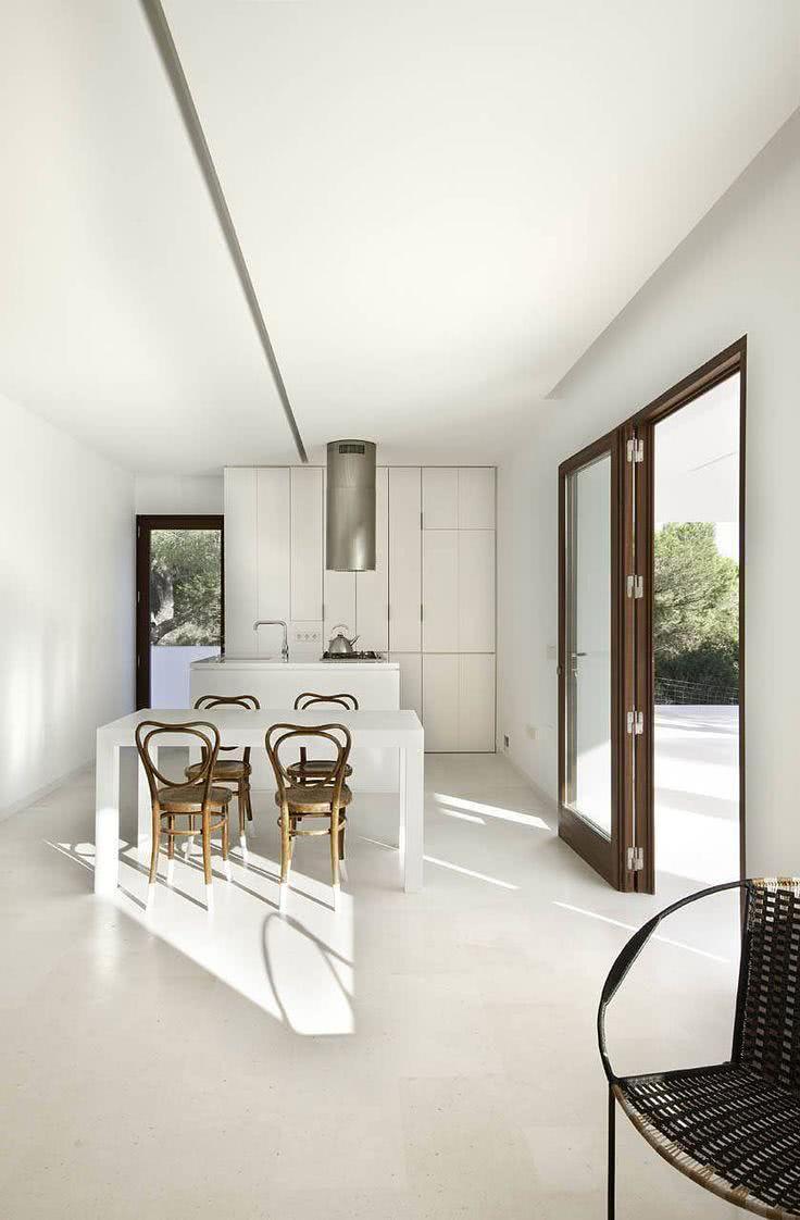 Cozinha moderna minimalista branca com cadeiras de madeira antiga