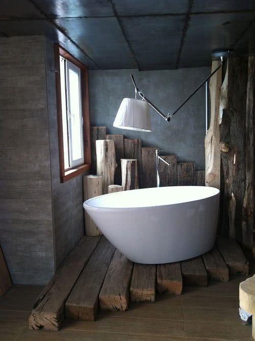 Banheira branca com suportes de troncos de madeira