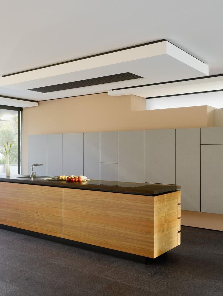 Cozinha com armários sem puxadores, ilha de madeira com bancada preta