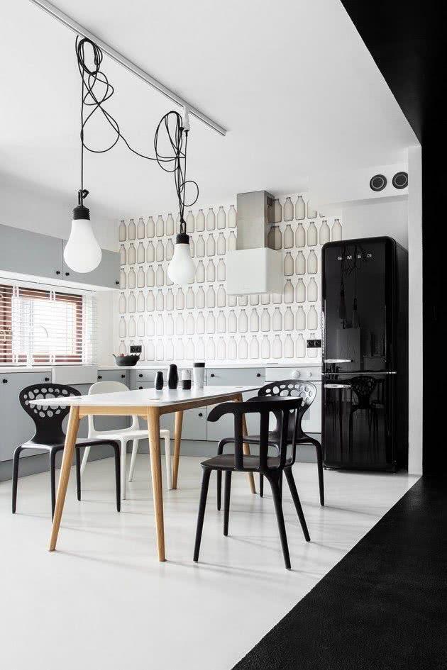 Proposta de cozinha que combina a geladeira preta com as cadeiras da mesa de jantar