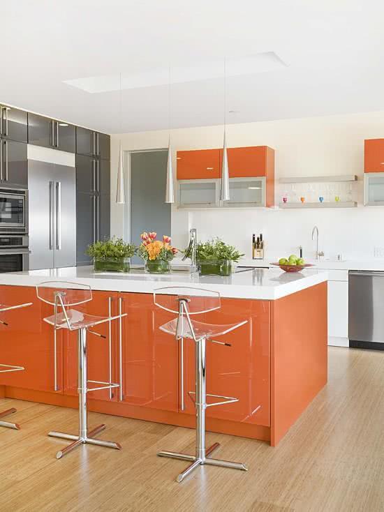 Cozinha clara com armários de inox e ilha laranja