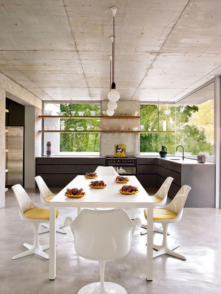 Cozinha com concreto, móveis grafite e mesa branca