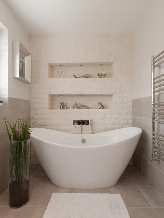 Banheira branca ondulada, banheiro com parede e tijolinho branco